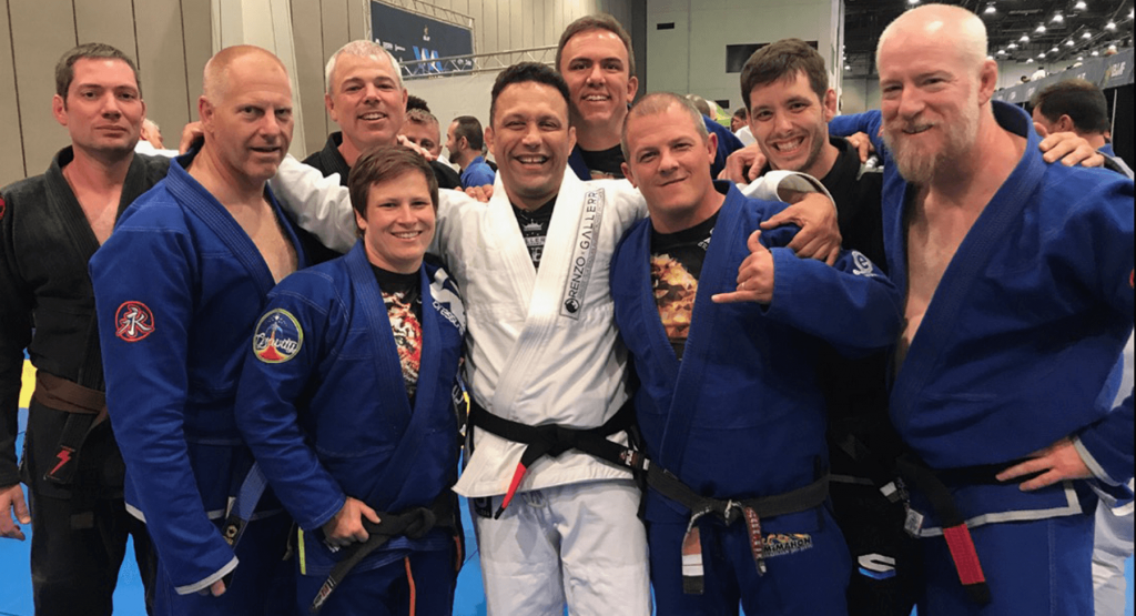9 jiu jitsu practioners from right to left, rob, bill, julie, nate, renzo gracie, jamis, finnie mcmahon, bruce, garry