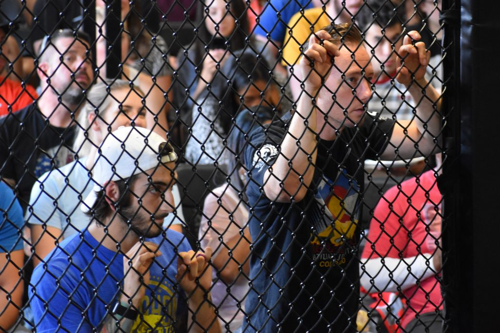 two muay thai coaches watching a fighter compete behind a MMA cage
