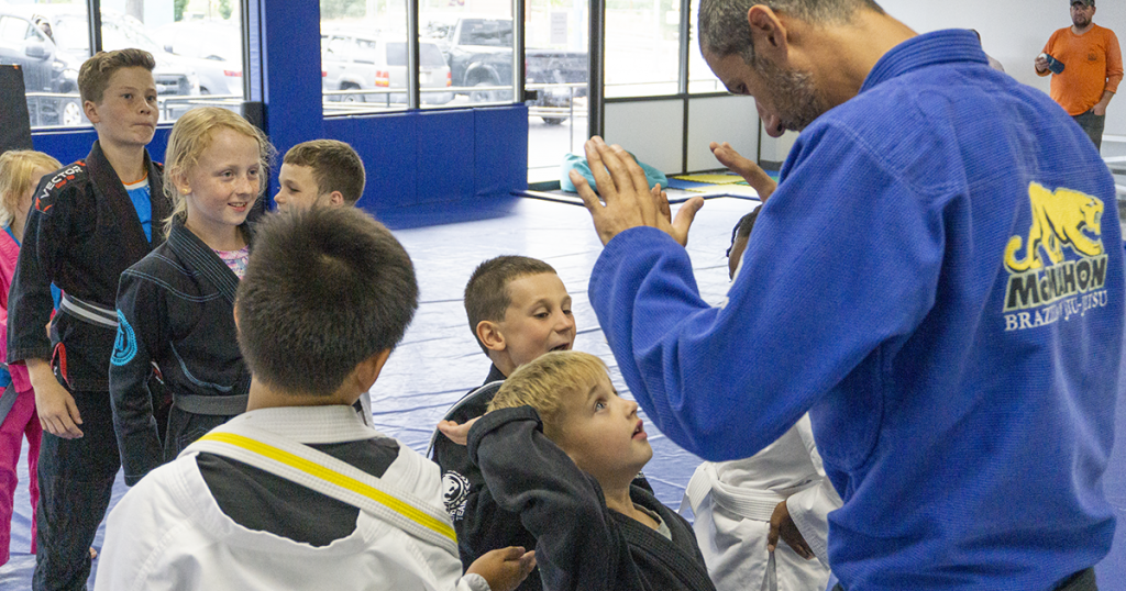 jiu jitsu black belt in blue gi high fiving child martial artist